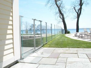 Painted stainless steel and tempered glass swimming pool fence and gates at private residence designed by Hugh J. Collins Jr. Landscape Designer, Inc.