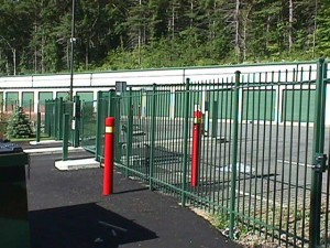 Wrought iron slide gates with monitored gate controls at storage facility.
